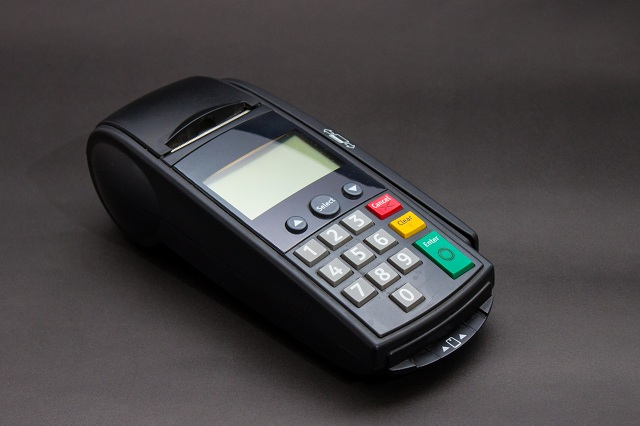 Hand Swiping Credit Card In Store. Female hands with credit card and bank terminal. Color image of a POS and credit cards