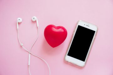 red-heart-between-the-earphone-and-smartphone-on-pink-background_23-2147889265