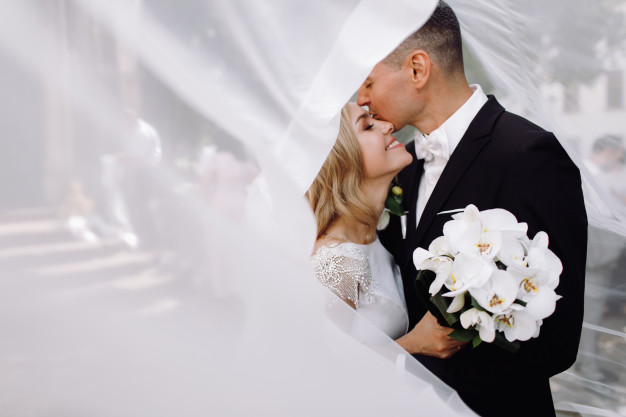 groom-black-tuxedo-hugs-tender-stunning-bride-while-they-stand_8353-8050