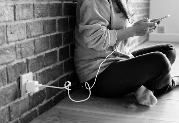 young-woman-using-smartphone-as-it-is-being-charged_53876-13379